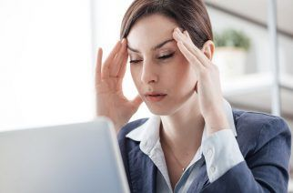 Exhausted businesswoman in her office with head in hands, she is having a bad headache, overwork and stress concept