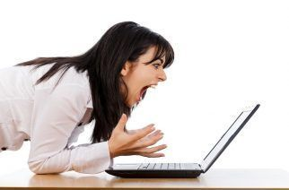Woman screaming nervously at the laptop isolated on white.